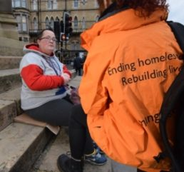 outreach worker and woman on steps
