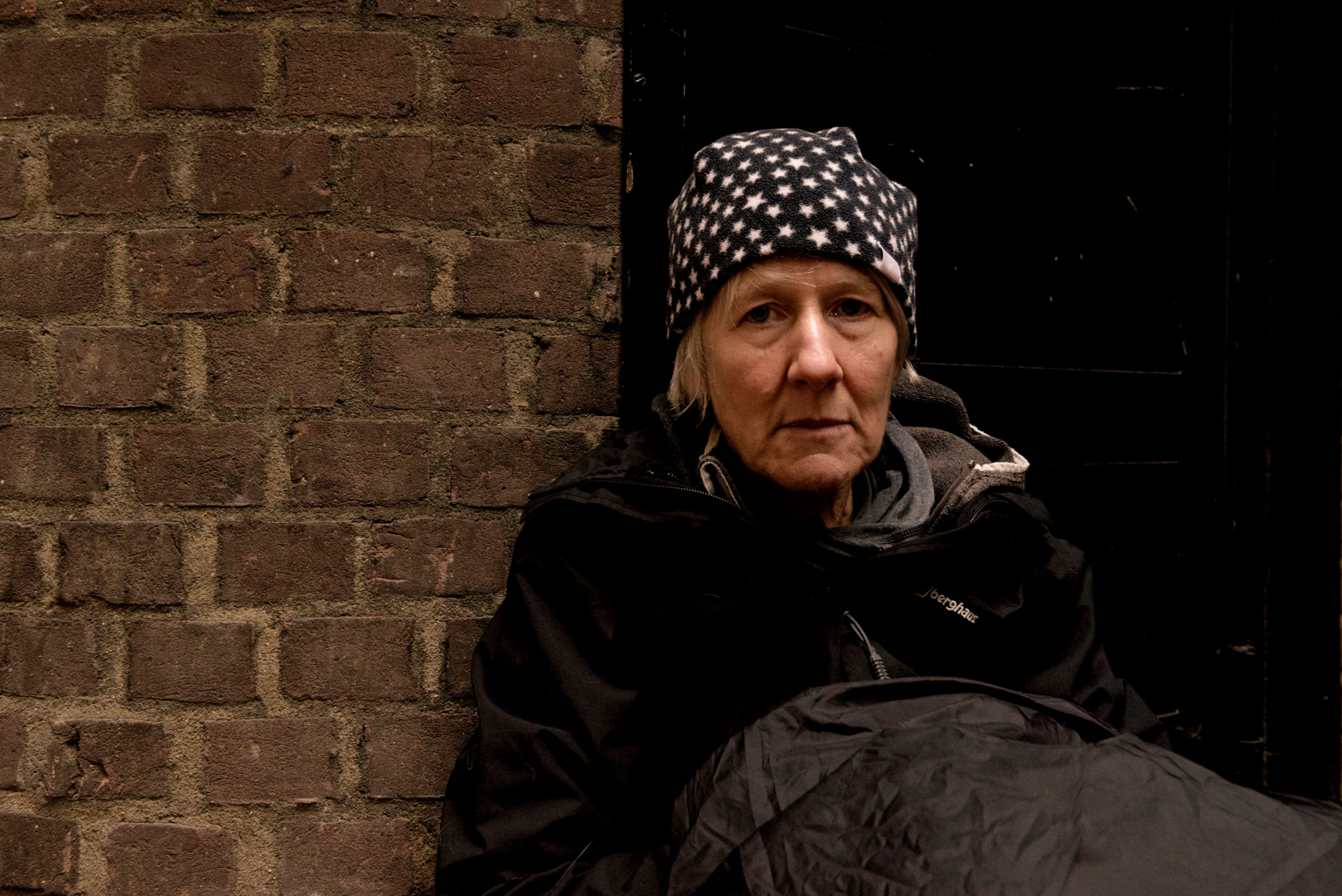 A woman sits on the floor next to a brick wall